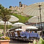 Tische und Sonnenschirme im Hardenberg BurgHotel mit Blick auf die BurgRuine